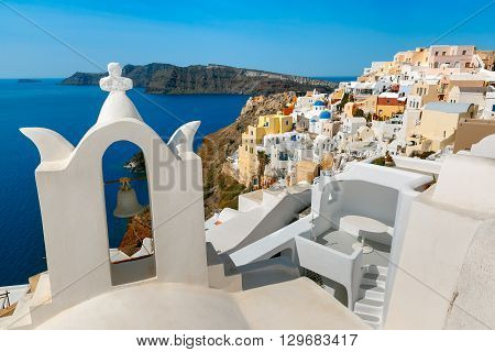Arch with a bell, white houses and church with blue domes in Oia or Ia, island Santorini, Greece