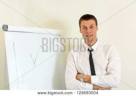 Confident young man in front of a flipchart
