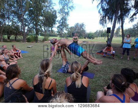 NORTH SHORE HAWAII - FEBRUARY 26: AcroYoga Teacher Jason Nemer balances instructor as class watches demonstration at Wanderlust yoga event on the North Shore Hawaii on February 26 2016.
