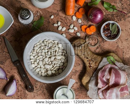 White beans bacon carrots red onion spices and herbs - ingredients for making bean mash with bacon. On a stone background. Top view