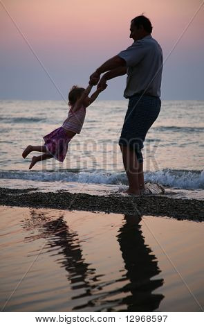 Grandfather rotates child on sunset at sea