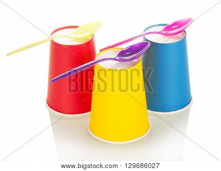 Bright disposable cups and spoons isolated on white background