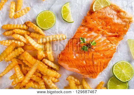 Delicious red fish salmon steak fillet with French curly fries on a white parchment paper with sliced lime and parsley on a wooden table studio lights close-up