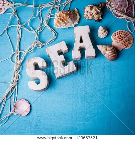 Beautiful sea composition wooden letters and fishing net on blue background