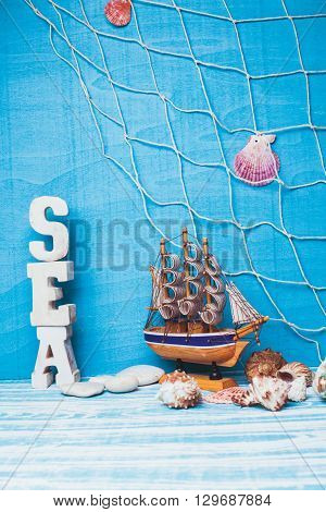 Beautiful sea composition with toy sailboat, seashell, glass bottle and fishing net on blue background