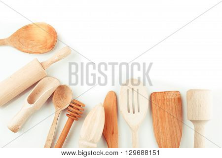 Assortment of wooden kitchen utensils on a white background