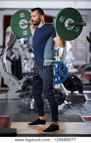 Man Doing Squats With Barbell On Neck