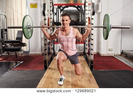 Man doing barbell lunges to train legs in the gym