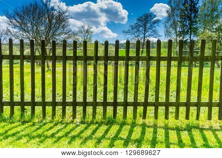 Landscape with old wooden railing with cloudy dramatic sky and trees. Grass field with fence cloudy sky and beautiful nature.