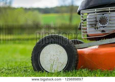 Detail of wheel and piece of motor of lawn mower (grass cutter) on cutted grass with wooden railing grass field trees and sky on background. Soft focus / shallow of depth