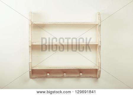 Empty wooden shelf with three hooks on the isolated background