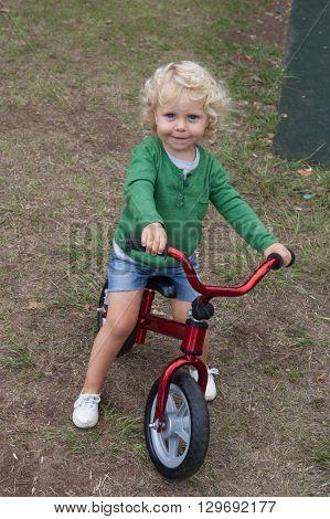 Little kid riding his bike down the street
