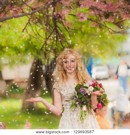 Girl under the sakura tree with flowers in hands enjoys the blossom