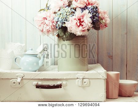 Flowers in a blue vintage can on white retro bag and kitchen earthenware