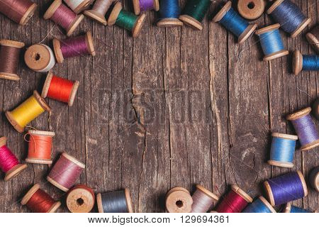 Retro wooden sewing spools with colourful threads over vintage wooden background