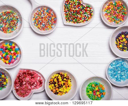 Various color sprinkles in a white bowls