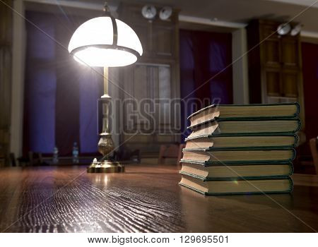 piles of books on table in library hall (Shallow depth of field)