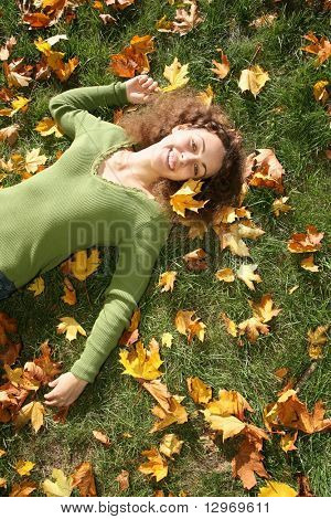 woman with the yellow leaf lies on the grass