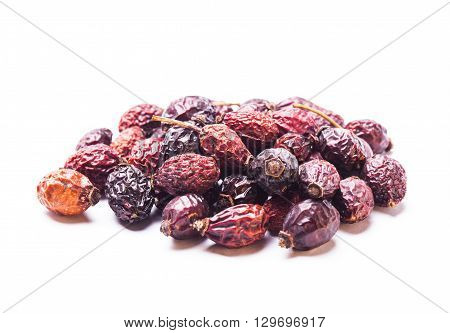 A pile berries of dried rosehips  isolated on white