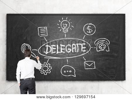 Businessman drawing delegating sketch on chalkboard, close up
