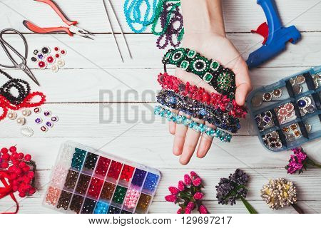 Plastic berries, flowers, beads and instruments for doing handmade headbands. Top view with hands