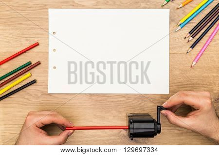 Top view of male hands sharpening red pencil on wooden desktop with blank white paper sheet. Mock up