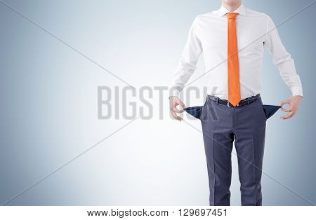 Unemployment concept with businessman showing empty pockets on grey background. Mock up