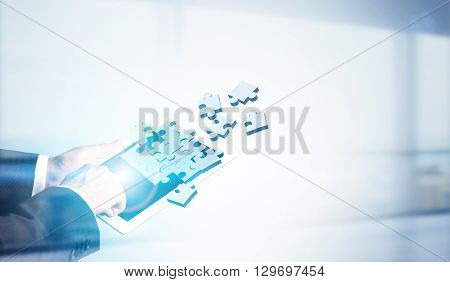 Businessman using tablet with digital puzzle pieces