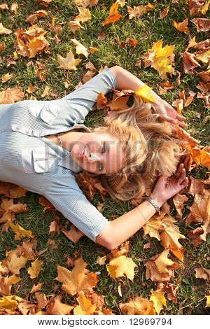 blue-eyed blond lies among yellow leaves 2