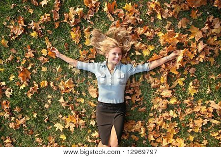 blue-eyed blond lies among yellow leaves