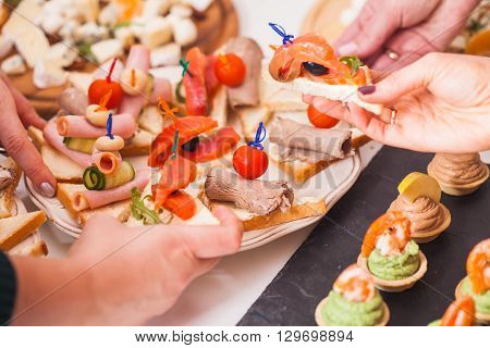 Close-up of a hands reaching out for a delicious sandwiches