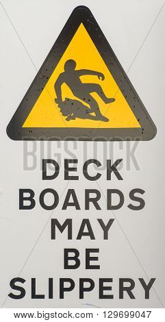 Health and safety hazard warning sign stating Deck Boards May Be Slippery When Wet for shipping or boat designs.