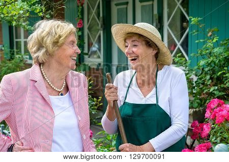 Two Senior Women Laughing Together In Garden