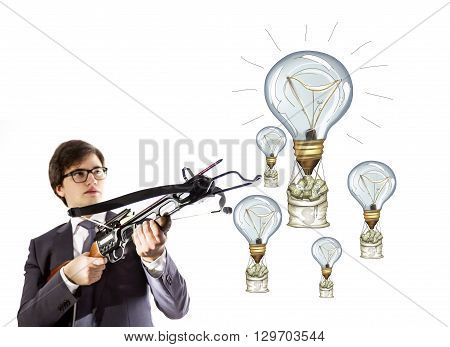 Success concept with businessman aiming at lightbulb airballoons and money sacks with crossbow