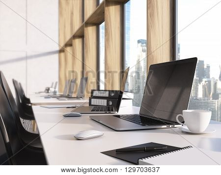 Closeup of blank laptop screen on desktop with coffee cup documents and other items in coworking office with new York city view. modern office with laptop on table. Mock up 3D Rendering