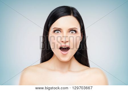 Headshot of surprised brunette woman, close up