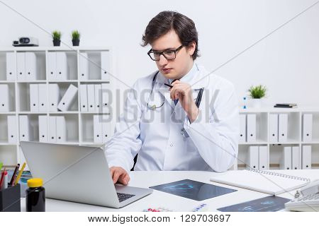Young handsome doctor using laptop placed on office desk with x-rays and other items