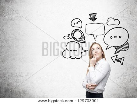 Thinking businesswoman with speech and thought bubbles on blank concrete wall