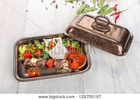 BBQ salad, meat, tomatoes, peas, peppers, pita bread, sauce in a copper bowl on a white wooden background