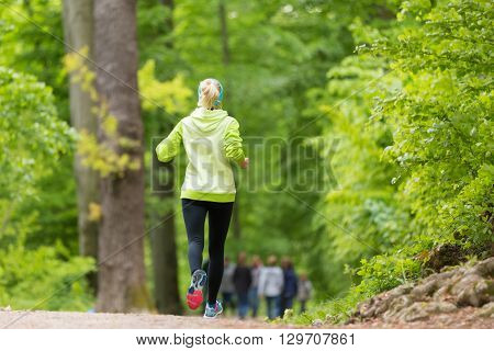 Sporty young female runner in forest.  Running woman. Female runner during outdoor workout in nature. Fitness model outdoors. Weight Loss. Healthy lifestyle.