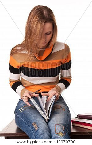 Young Student Sitting On The Desk And Leafs Book