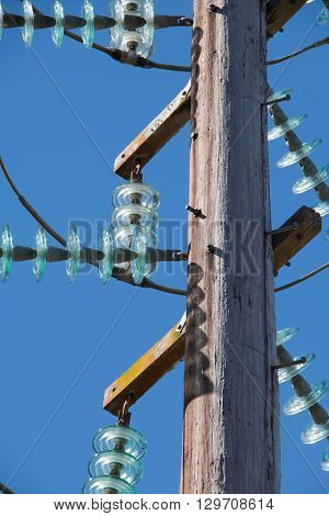 powerline with glass insulators against blue sky
