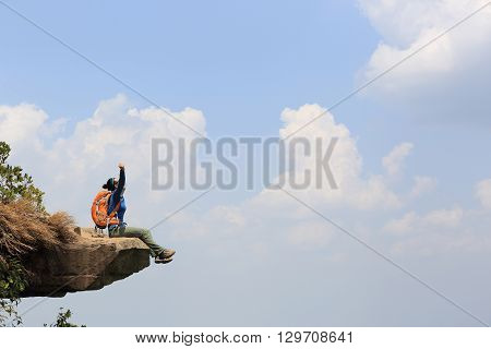 cheering young woman backpacker on mountain peak cliff