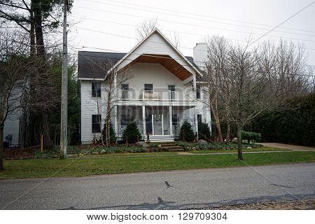 HARBOR SPRINGS, MICHIGAN / UNITED STATES - DECEMBER 23, 2015: A large home with a front porch and a balcony on Second Street in Harbor Springs.