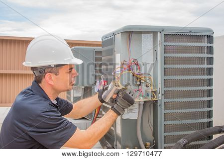 Hvac Tech checking a run capacitor on a condenser