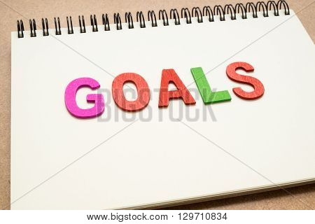 Text GOALS wording on open spiral notebook - colorful GOALS uppercase letter on open notebook