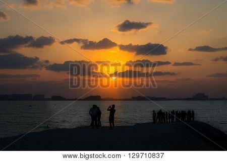 Tourists Enjoying The Sunset And The Atlantis Hotel