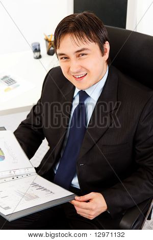 Smiling modern businessman sitting at office desk and working with financial documents