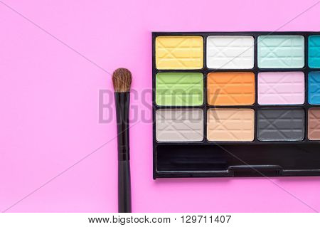 Colorful eyeshadow palette with eye make up brush - colorful cosmetics on bright pink background