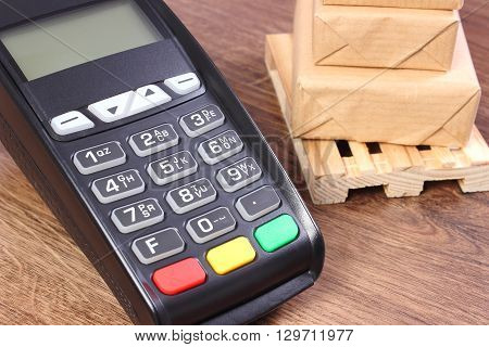 Credit card reader payment terminal and small wrapped boxes on wooden pallet cashless paying for products and shipping finance concept
